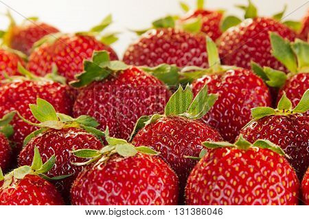 Strawberry background of whole strawberries in sunlight. Colorful ripe berries strawberries. Fruit background. Strawberry pattern. Spring background. Summer background. Top view. Macro. Texture.