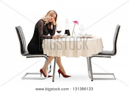 Lonely young woman sitting at a restaurant table and drinking wine isolated on white background