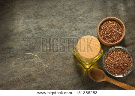 linseed oil in bottle and flax seeds on table background