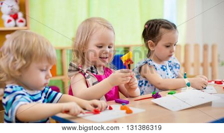 Kids making arts and crafts. Children in kindergarten.