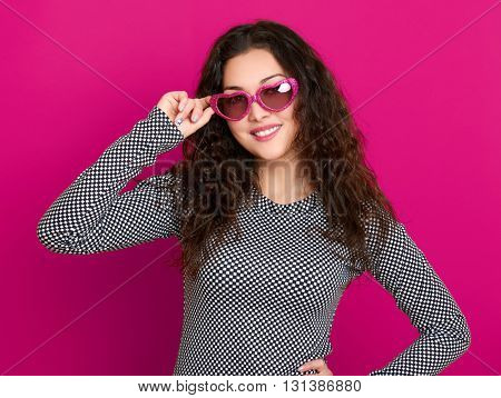 young woman beautiful portrait, posing on pink background, long curly hair, sunglasses in heart shape, glamour concept