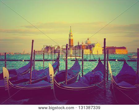Gondolas moored by Saint Mark square vintage toned. View of the San Giorgio di Maggiore from Piazza San Marco - Venice Venezia Italy Europe