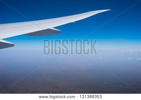 Wing of airplane flying above the clouds in the sky