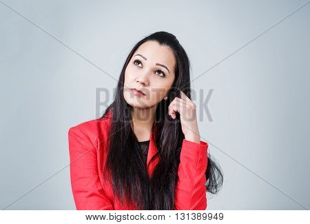 Young thoughtful woman on the gray background