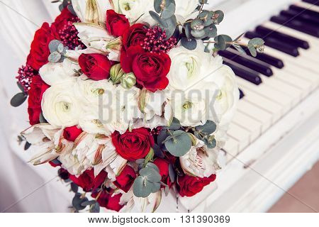 Bridal bouquet with red and burgundy colors lay on piano