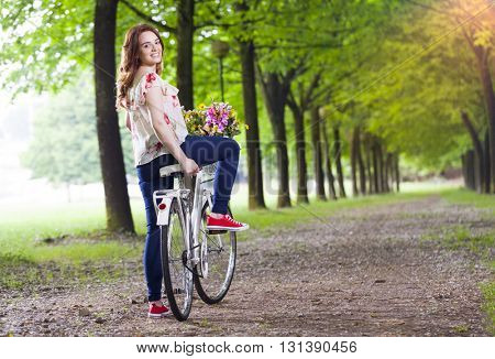 Beautiful young woman standing with a vintage bicycle at the park