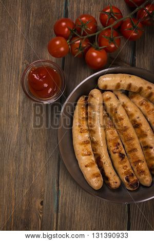 Roasted sausages with fresh vegetables over rustic background. Toned image. Top view