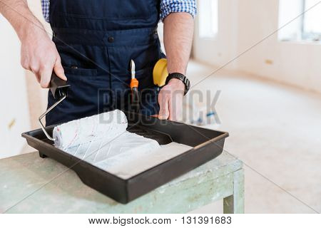 Close-up of mans hands using paint roller while working indoors