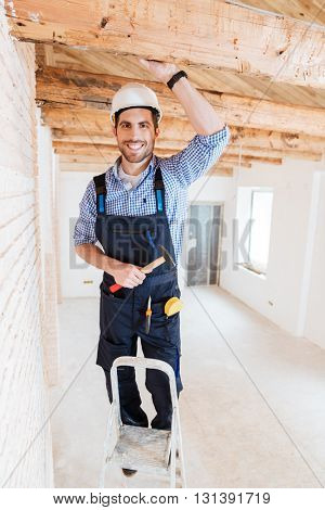 Smilling worker standing on the ladder and holding a hammer indoors