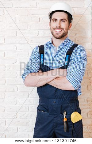 Joyful young builder keeping arms crossed and smiling while standing indoors