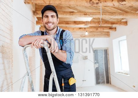 Handsome builder smilling and holding pc tablet in his hands indoors