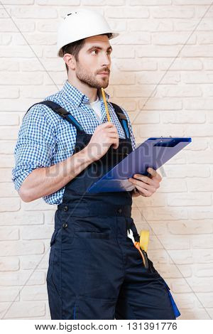 Portrait of a handsome engineer using clipboard to write something while working indoors