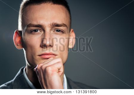 Closeup portrait of a serious businessman looking at camera over gray background