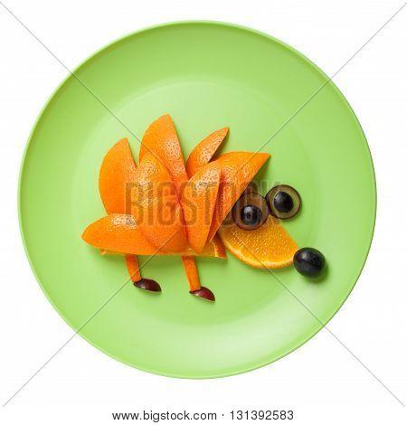 Hedgehog made of orange and grape on green plate