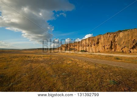 Wonderful landscape. The road stretches into the distance in the desert under a blue sky and clouds line. Sunny day in Cyprus the Akamas peninsula. Perspective. Wide angle.