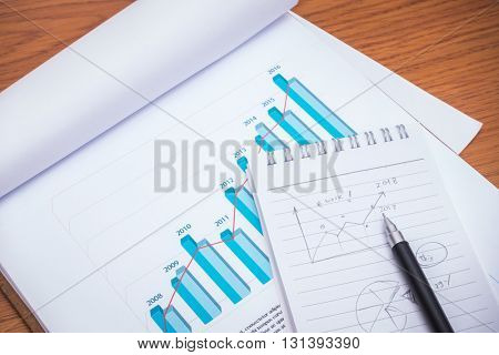 Financial charts with pencil on table