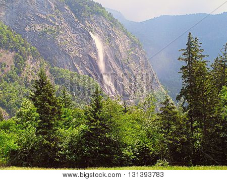 Small waterfall in the Alps mountains in summer.