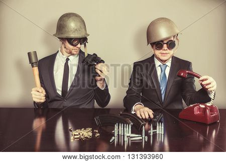 Two vintage military businessman sitting at office desk with military stuff