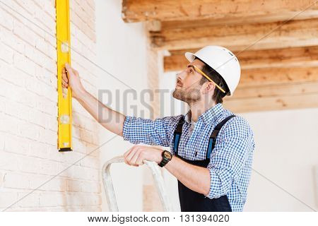 Close-up portrait of a builder holding construction level against the wall and standing on the ladder indoors