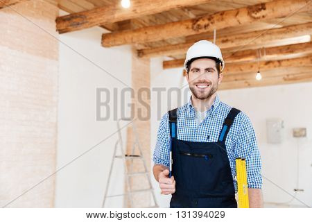 Smiling cheerful builder standing and holding tools in the working place indoors