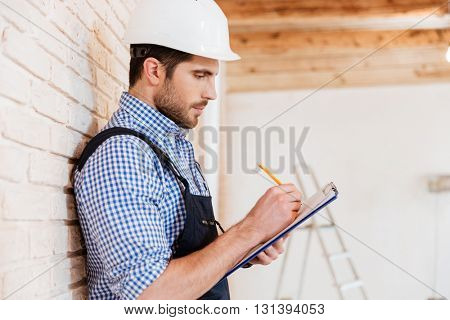 Pensive builder standing backwards to the wall with clipboard in his hands