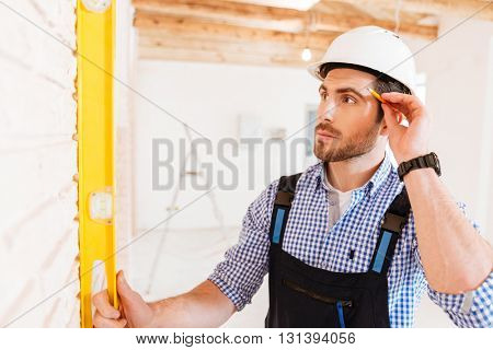 Close-up prtrait of a smart concentrated builder indoors at the working area