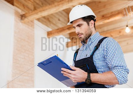 Happy builder writing something in hardhat with clipboard in his hands
