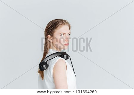 Young woman standing with retro phone tube on the shoulder and looking at camera isolated on a white background