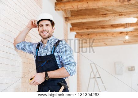 Smilling builder handyman standing at the worikng place and holding yellow tape