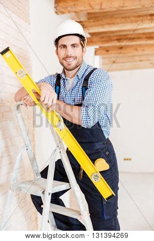 Close-up portrait of a smiling worker standing on the ladder and holding construction yellow level inoors
