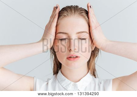 Beauty portrait of relaxed woman with closed eyes posing on white background