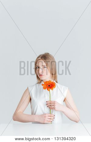Beauty portrait of attractive blonde woman sitting at the table and holding flower isolated on a white background