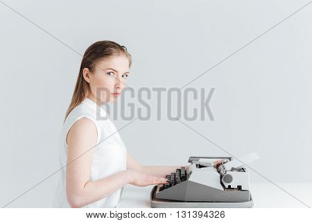 Young woman typing on retro machine and looking at camera isolated on a white background