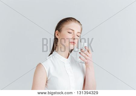 Beauty portrait of relaxed woman with fresh skin holding glass of water isolated on a white background
