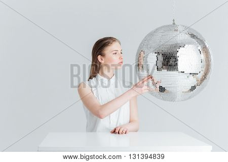 Beauty portrait fo a young woman sitting at the table with mirror ball isolated on a white background