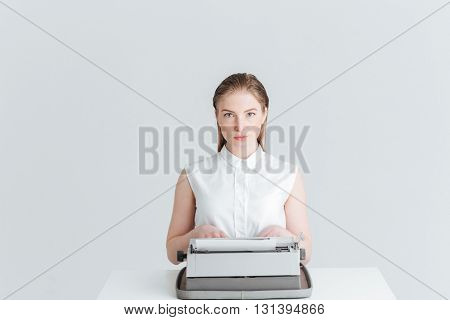 Young woman sitting at the table and typing on retro machine isolated on a white background
