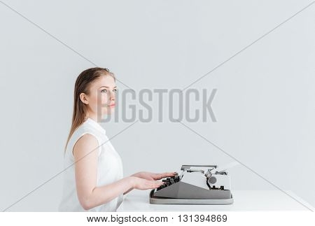 Pensive woman typing on retro machine isolated on a white backgound