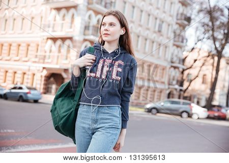 Pensive charming young woman with backpack listening to music and walking in the city