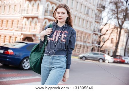 Attractive young woman with backpack walking and listening to music from smartphone in the city