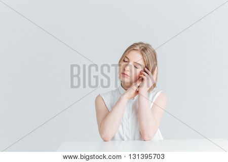 Beauty portrait of a young relaxed woman sitting at the table isolated on a white background