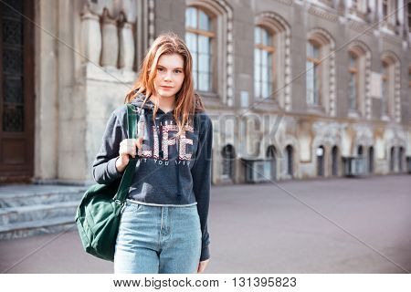Portrait of attractive young woman in jeans and hoodie with backpack in old city