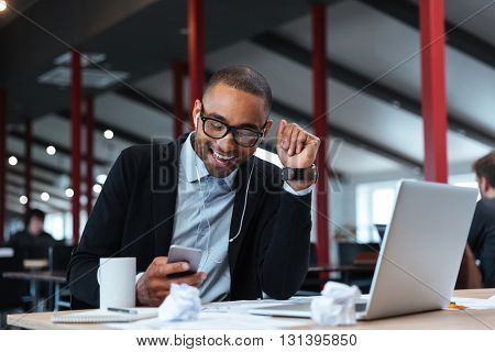 Happy businessman smiling and texting on the smartphone at the table