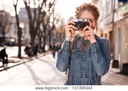 Concentrated cute young woman standing and taking pictures outdoors using old vintage camera