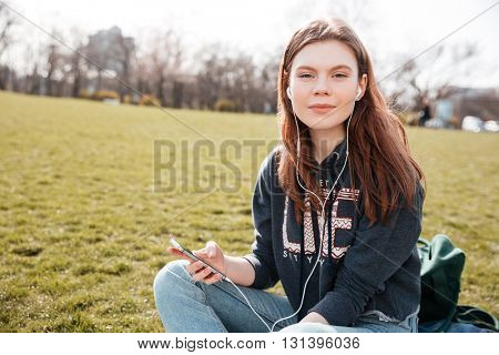 Pretty peaceful young woman listening to music from mobile phone on the lawn