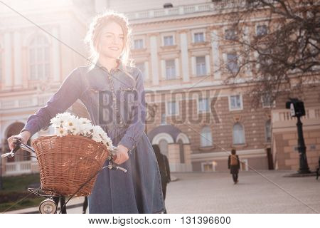 Smiling charming young woman standing with bike in the city