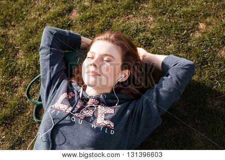 Top view of happy relaxed young woman lying on grass and listening to music