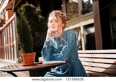 Thoughtful lovely young woman sitting and reading a book in outdoor cafe