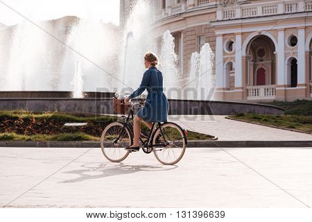 Pretty young woman riding a bike near fountain in the city