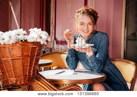 Cheerful attractive young woman smiling and eating cupcake in outdoor cafe