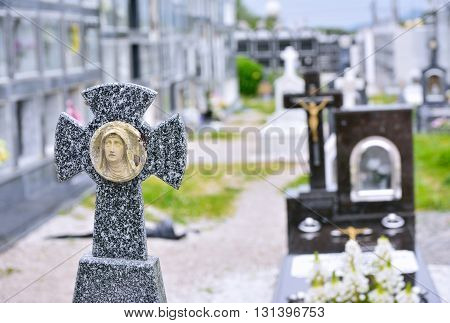 Close-up of marble tombstone with cross against of unfocused graveyard